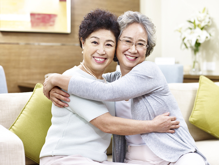 singaporean: two senior asian women sitting on couch hugging each other, happy and smiling Stock Photo