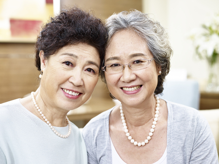 ancianos felices: portrait of two senior asian women looking at camera smiling