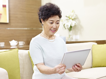 woman on couch: senior asian woman sitting on couch looking at tablet computer Stock Photo