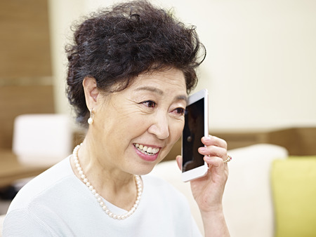 conversing: senior asian woman sitting on couch talking on mobile phone