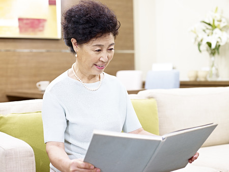 woman on couch: senior asian woman sitting on couch reading a book