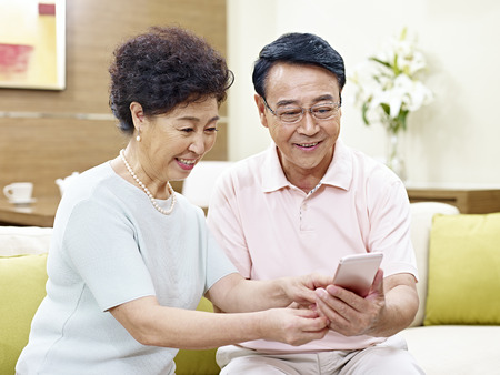 senior asian couple sitting on couch looking at cellphone together, happy and smiling
