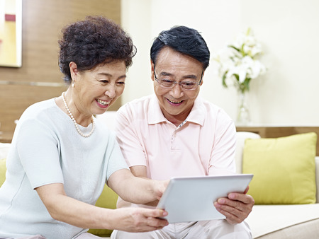 couple relaxing: senior asian couple sitting on couch looking at tablet computer together, happy and smiling