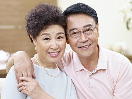 closeup portrait of a senior asian couple looking at camera smiling