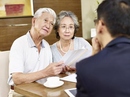 desconfianza: Pares asiáticos mayores que parece estar confundido después de leer una propuesta