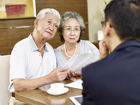senior asian couple appear to be confused after reading a proposal Stock Photo