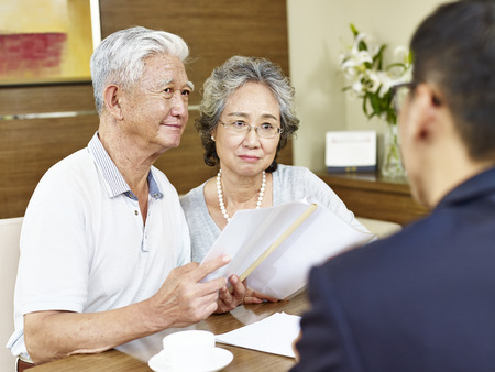 senior asian couple appear to be skeptical after reading a proposal Stock Photo