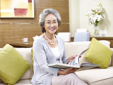 Senior Aziatische vrouw zittend op de bank thuis bedrijf een boek kijken camera glimlachen.