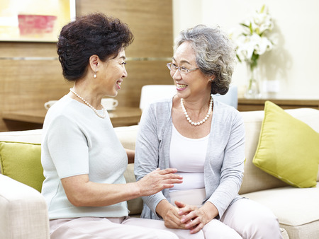 two asian senior woman sitting on sofa chatting, happy and smiling.