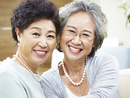 companions: close-up portrait of a happy senior asian couple looking at camera smiling.