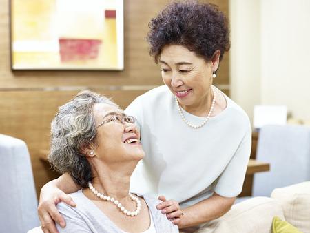 women friendship: two senior asian women showing care and friendship