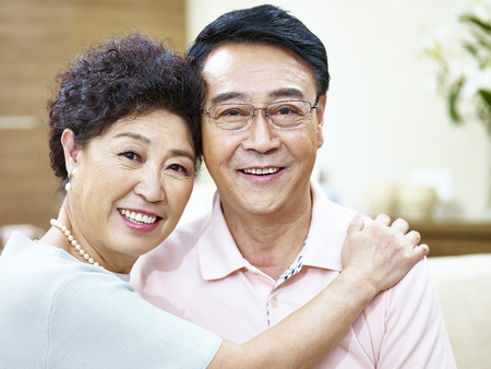 singaporean: portrait of a happy senior asian couple looking at camera smiling.