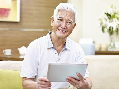 senior asian man sitting on sofa holding a tablet computer looking at camera smiling.