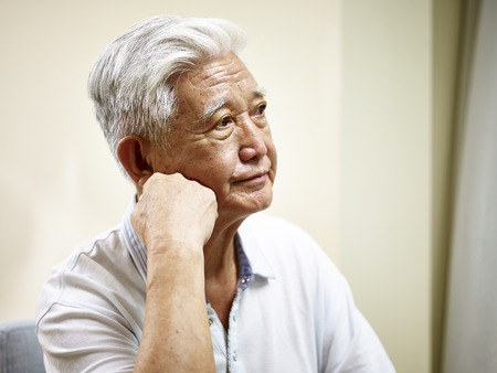 east asian: portrait of sad senior asian man hand on chin, side view.