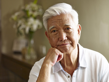 portrait of sad senior asian man hand on chin, frontal view.