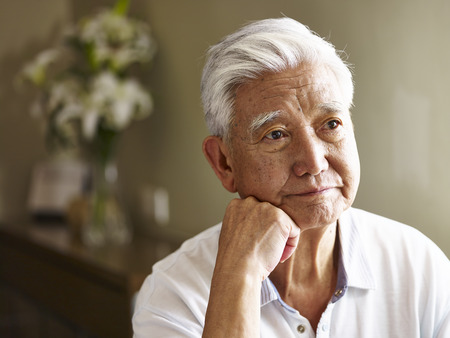 portrait of sad senior asian man hand on chin.