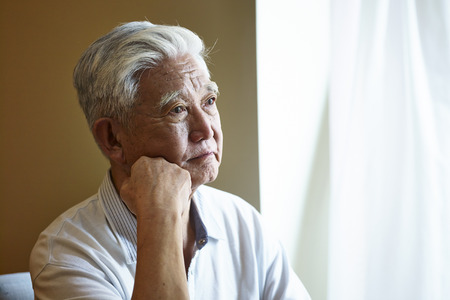 portrait of a sad asian senior man sitting by the window hand on chin.