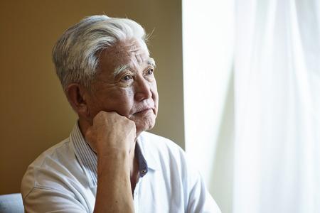 Portret van een trieste Aziatische senior man die aan de kin bij het raam zit.