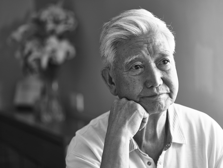 black and white portrait of a sad lonely asian senior hand on chin looking away thinking. Stock Photo