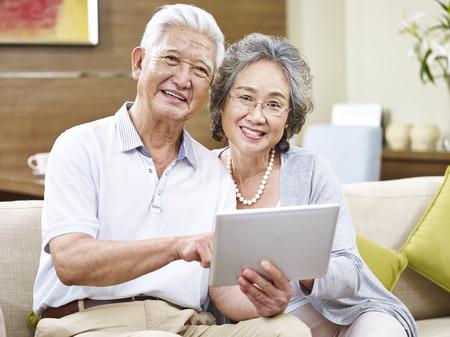 笑みを浮かべてカメラを見ているタブレット コンピューターと幸せなアジア シニア カップル。
