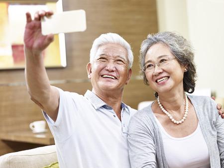 Heureux couple senior asiatique prenant un selfie en utilisant un téléphone mobile.