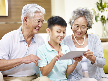 happy asian grandfather and grandmother looking at tablet computer with grandson, happy and smiling.