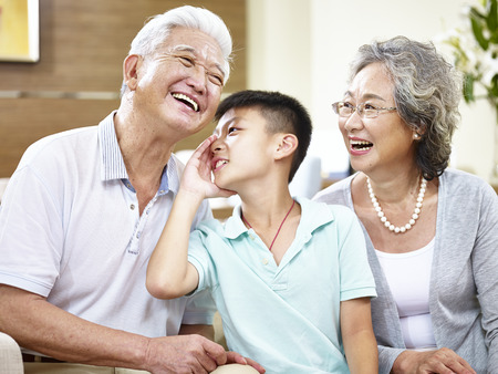asian grandson whispering to grandfather while grandmother watching.