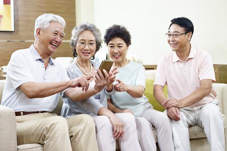 kleine groep van hogere Aziatische mensen het delen van content op mobiele telefoon tijdens het verzamelen.