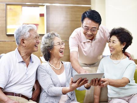 使用して良い時間を持つアジアのシニアのカップルは一緒にコンピューターをタブレットします。