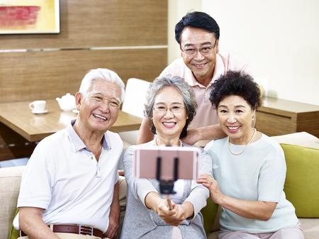 두 행복 고위 아시아 커플 스틱에 핸드폰을 사용 하여 셀을 복용.