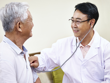 asian doctor checking senior patient using a stethoscope. Imagens