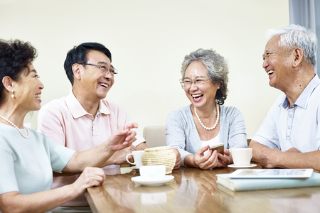 small group of senior asian people getting together talking and laughing