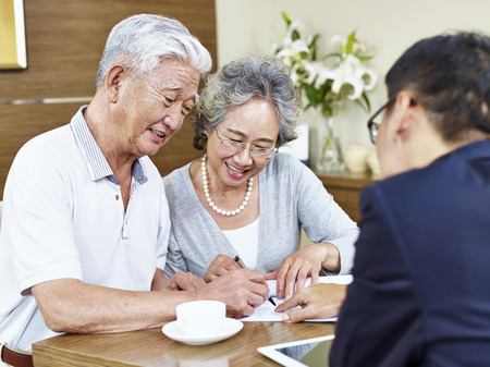 happy senior asian couple signing a contract agreement in front a salesperson.