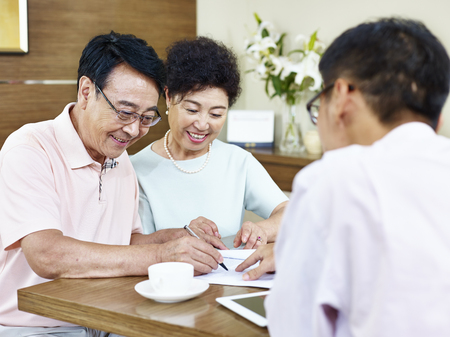 happy senior asian couple signing a contract agreement in front a sales person.