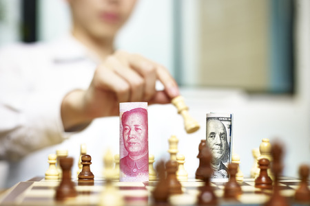 monetary policy: U.S. Dollar (USD) and Chinese Yuan (CNY or RMB) bills on a chess board, concept for currency games.
