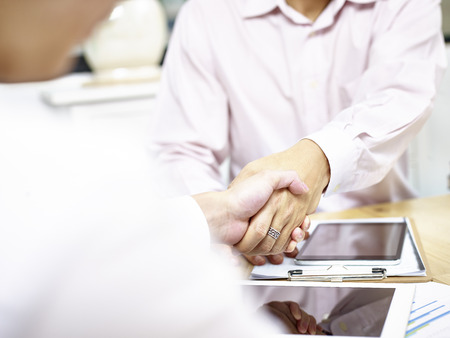 two male business executive shaking hands over desk in office. Stock Photo