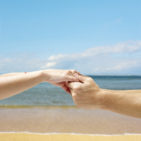 hands of a young couple held together against a sky, sea and beach background.