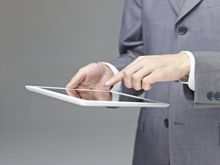 business person in suit using a tablet computer, side view, gray background.