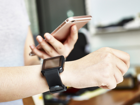 syncing: closeup shot of hands of a woman using smartphone and smartwatch together.