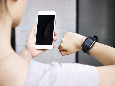 synchronizing: closeup shot of hands of a woman using smartphone and smartwatch together.