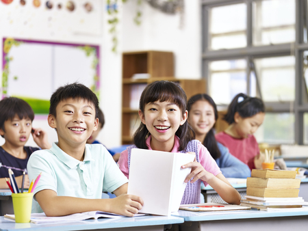 elementary age girl: portrait of asian elementary school students in classroom looking at camera smiling.