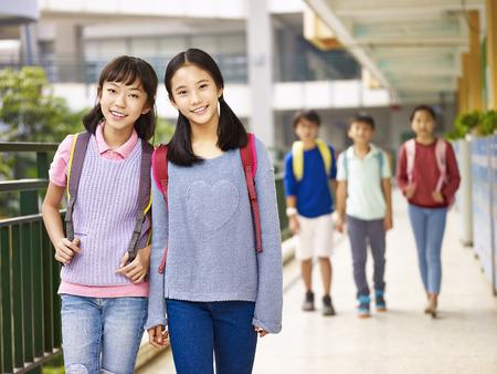 Aziatische basisschoolmeisjes lopen in klaslokaalgebouw.