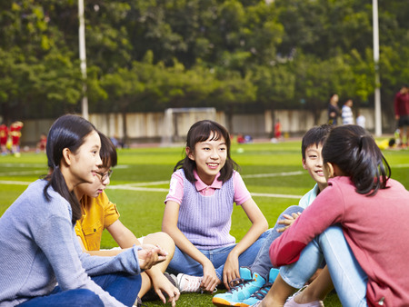 groep van Aziatische basisschool jongens en meisjes zitten en chatten op speelplaats gras