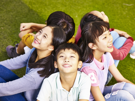 group of asian elementary school boys and girls sitting on playground grass looking up at the sky