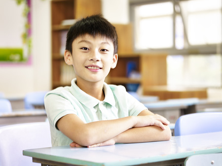 Retrato de un estudiante de once años de edad escuela primaria asiática sentado en el aula. Foto de archivo - 73362788