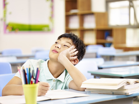 asian elementary schoolboy thinking while doing homework in classroom, looking up hand on cheek.