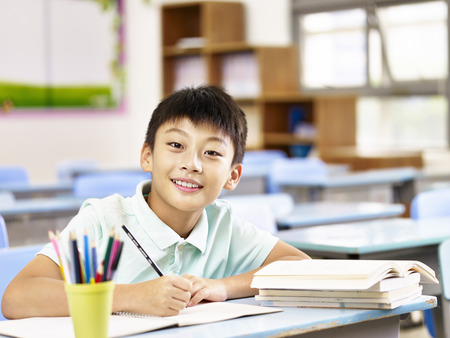 happy asian elementary school boy studying in classroom, looking at camera smiling. Stock Photo