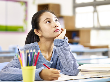 asian elementary schoolgirl looking up and thinking while studying in classroom. Stock Photo