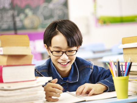 asian boy: happy asian elementary school boy studying in classroom smiling.