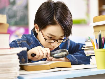Aziatische leerling met een bril met een vergrootglas om de woorden in een dik boek te vergroten.